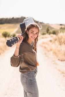 Bela adolescente segurando violão