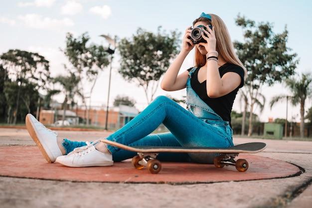 Bela adolescente sentada em um skate ao ar livre, tirando fotos com uma câmera.