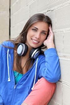 Bela adolescente sentado do lado de fora com fones de ouvido