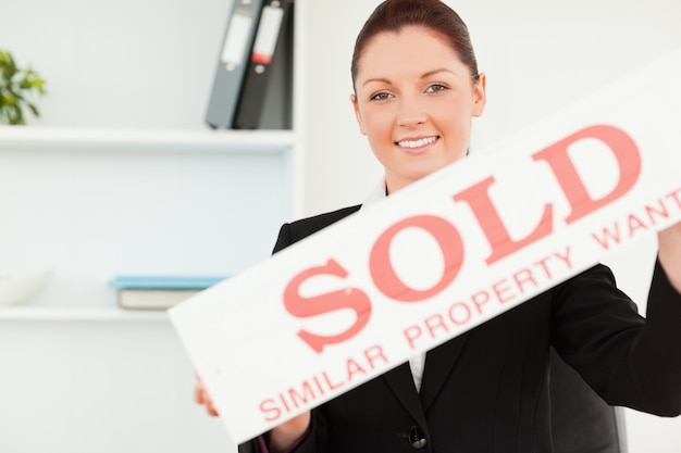Bela agente imobiliário segurando um cartaz vendido