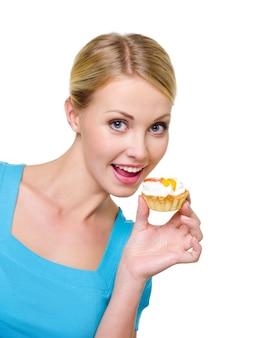 Bela alegria jovem feliz segurando um bolo doce perto do rosto