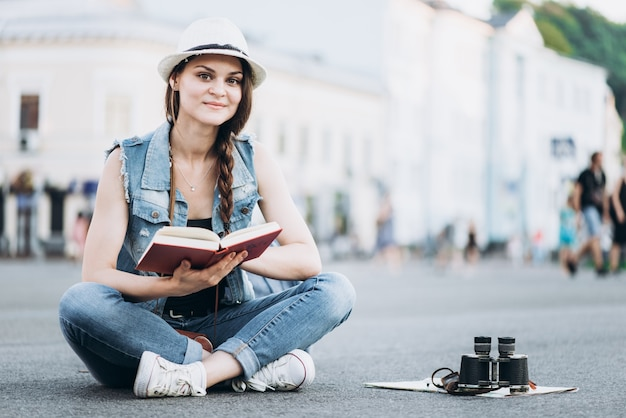 Bela aluna lendo um livro sentado no asfalto no meio da rua