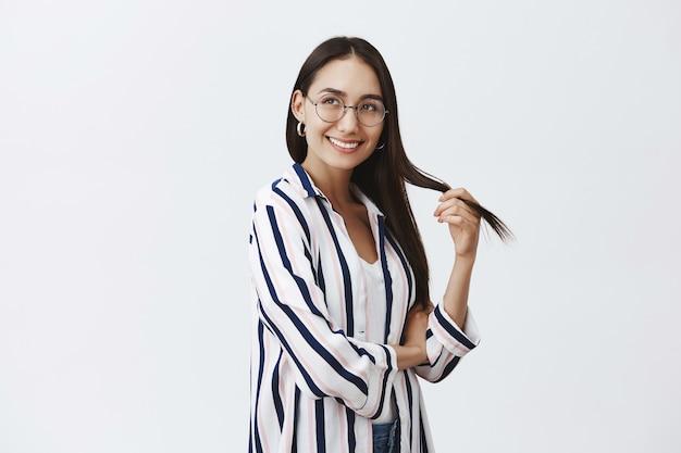 Bela aluna natural de óculos e blusa sobre camiseta, brincando com o cabelo e olhando com expressão sonhadora e alegre à esquerda, sorrindo largamente sobre a parede cinza