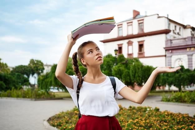 Bela aluna segurando pastas acima da cabeça, se escondendo da chuva.