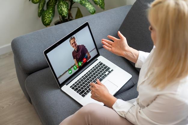 Bela aluna sorridente usando serviço de educação online. jovem mulher olhando no visor do laptop, assistindo o curso de treinamento e ouvindo-o com fones de ouvido. conceito moderno de tecnologia de estudo