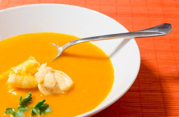 Bela apresentação da sopa de peixe em um prato branco sobre um fundo laranja.