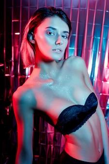 Bela arte sexy alta moda mulher em um fundo de néon vermelho brilhante