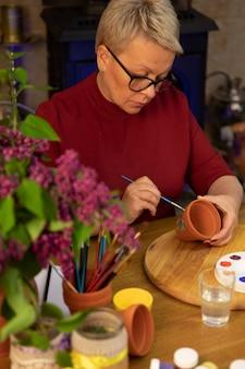 Bela artista pinta flores lilás em panela de barro no espaço de trabalho primavera estilo de vida