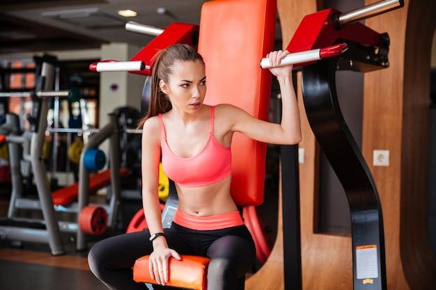 Bela atleta jovem e forte se exercitando na academia