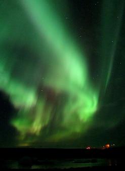 Bela aurora boreal dançando sobre a lagoa glaciar de jokulsarlon no sul da islândia