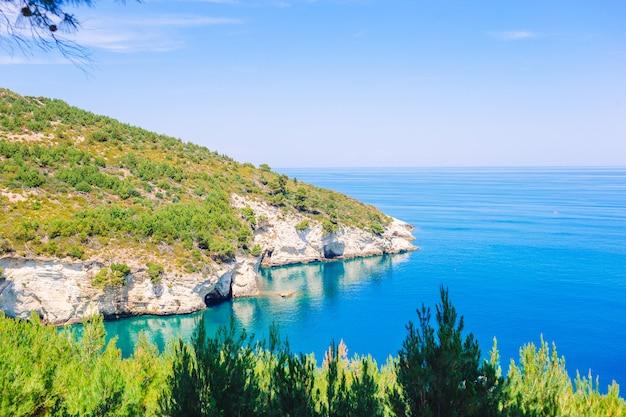 Bela baía acolhedora com barcos e água azul-turquesa na itália