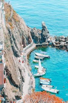 Bela baía acolhedora com barcos e águas turquesas claras na itália, europa