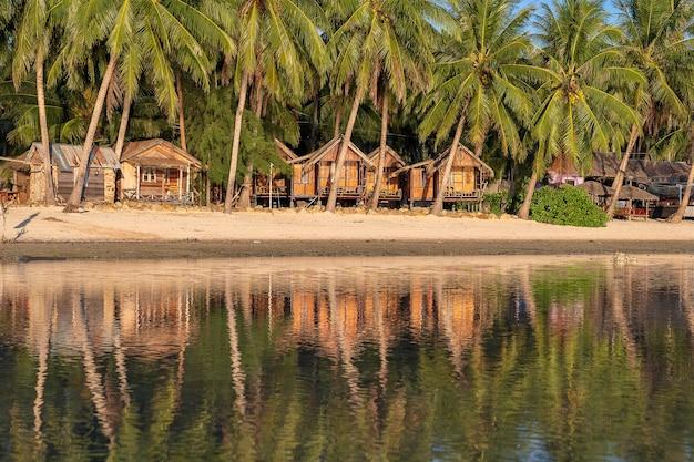 Bela baía com coqueiros e bangalôs de madeira que se refletem na água do mar. praia de areia tropical, folha de palmeira verde e água do mar na ilha de koh phangan, tailândia