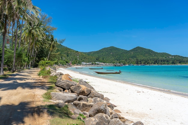 Bela baía com estrada de terra, água do mar azul, coqueiros e barcos. praia de areia tropical e água do mar na ilha de koh phangan, tailândia