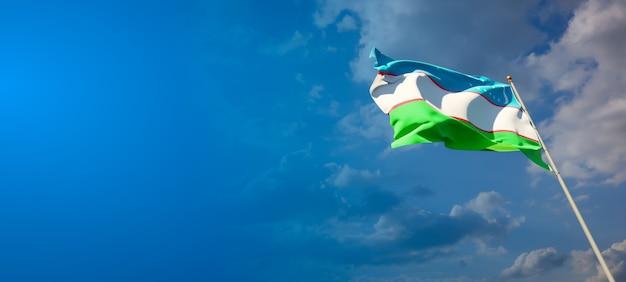 Bela bandeira do estado do uzbequistão no céu azul