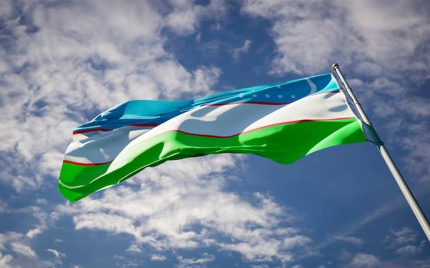 Bela bandeira do estado do uzbequistão tremulando no céu azul