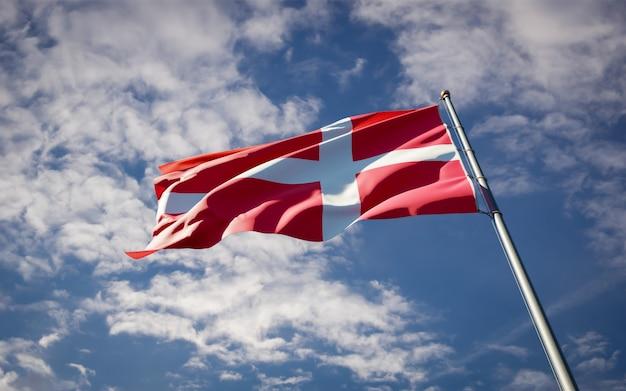 Bela bandeira do estado nacional da dinamarca tremulando no céu azul