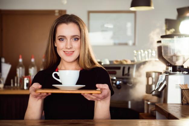 Bela barista feminino está trabalhando na cafeteria. mulher atraente está de pé atrás do balcão de bar, fazendo café e congratula-se com os clientes.