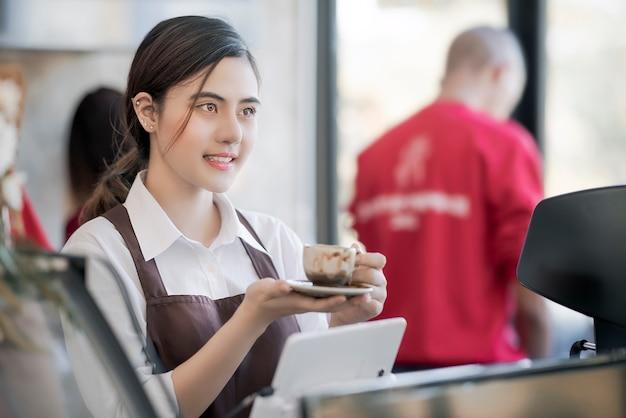Bela barista segurando xícara de café quente servido ao cliente com o rosto sorridente no bar coun