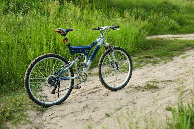 Bela bicicleta de montanha está na estrada de areia
