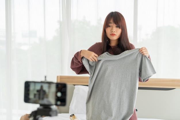 Bela blogueira asiática mostrando roupas na câmera para gravar vlog ao vivo em sua loja