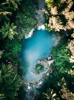 Bela cachoeira fluindo para o rio cercada por verdes