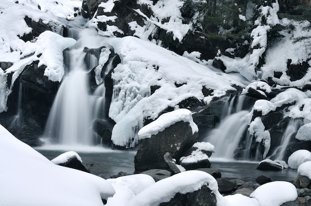 Bela cachoeira na montanha coberta de gelo