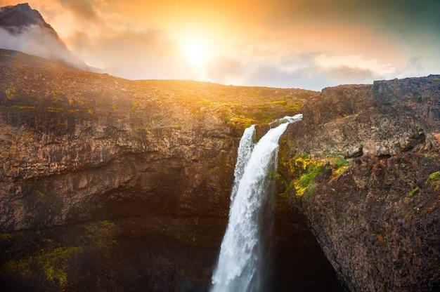 Bela cachoeira nas montanhas ao pôr do sol. ilha disco, costa oeste da groenlândia