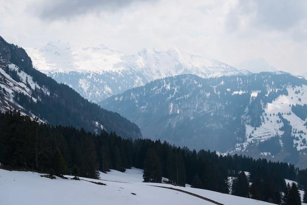 Bela cadeia de altas montanhas rochosas cobertas de neve sob um céu nublado