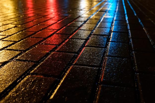 Bela calçada noturna na cidade depois da chuva