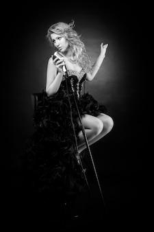 Bela cantora em vestido preto de concerto tocando jazz