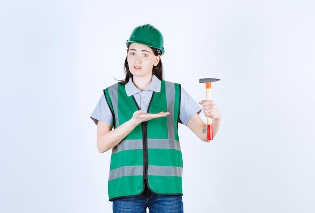 Bela capataz com uma jaqueta verde apontando o martelo na frente da parede cinza