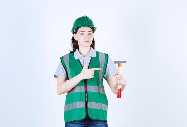 Bela capataz com uma jaqueta verde e boné verde apontando o martelo na frente da parede cinza