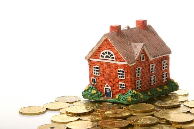 Bela casa e dinheiro ouro sobre fundo branco