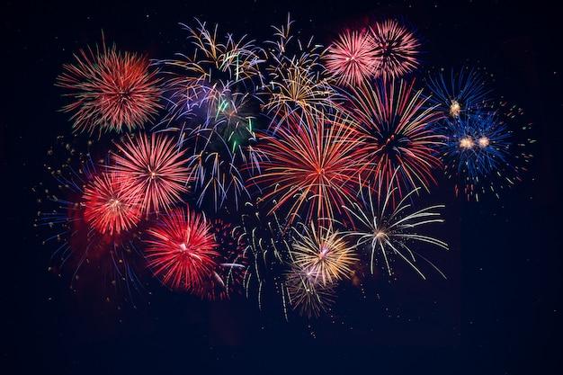Bela celebração dourado, vermelho, azul fogos de artifício cintilantes sobre o céu estrelado