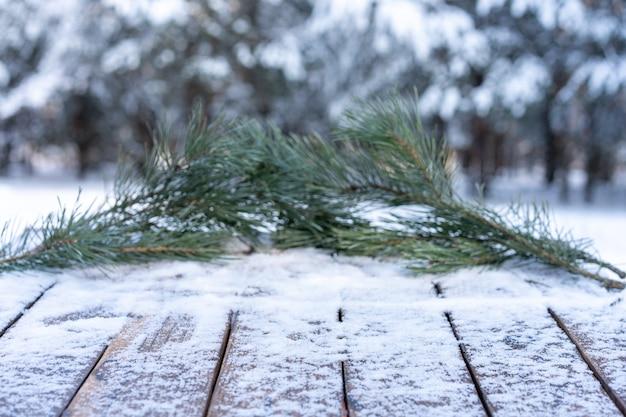 Bela cena de inverno. fundo desfocado de fundo de natureza de natal nevado, tampo da mesa de madeira no bokeh brilhante. para exibição de produto, simulação de época de natal