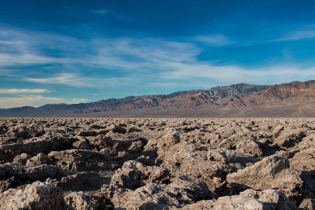 Bela cena de um terreno rochoso em um deserto e o céu azul brilhante no fundo