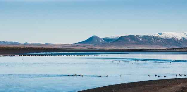 Bela cena de uma paisagem com altas montanhas nevadas e mar.