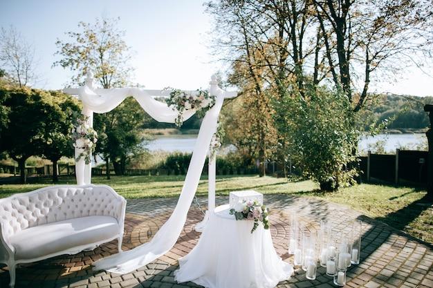 Bela cerimônia de casamento na margem do lago e arco com flores frescas