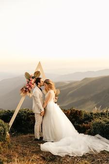 Bela cerimônia de casamento nas montanhas, casal de noivos apaixonados de mãos dadas e sorriso.
