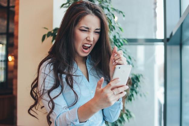 Bela charmosa morena brava menina asiática gritando no telefone no café