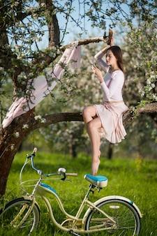 Bela ciclista feminina com bicicleta retrô no jardim primavera