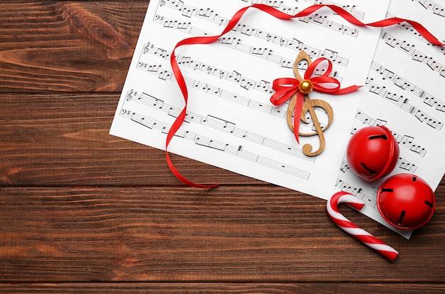 Bela composição com decorações e partituras em fundo de madeira. conceito de canções de natal
