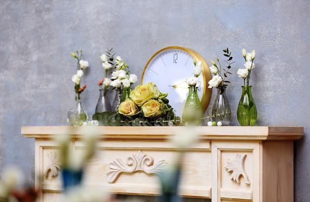 Bela composição com flores frescas e relógio na lareira