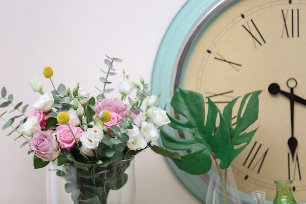 Bela composição com flores frescas e relógio vintage em fundo claro