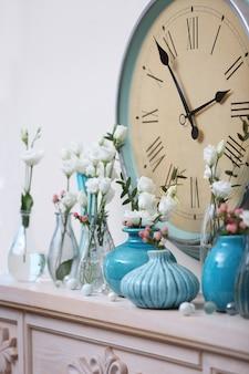 Bela composição com flores frescas e relógio vintage na lareira