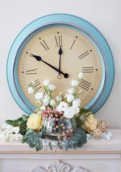 Bela composição com flores frescas e relógio vintage