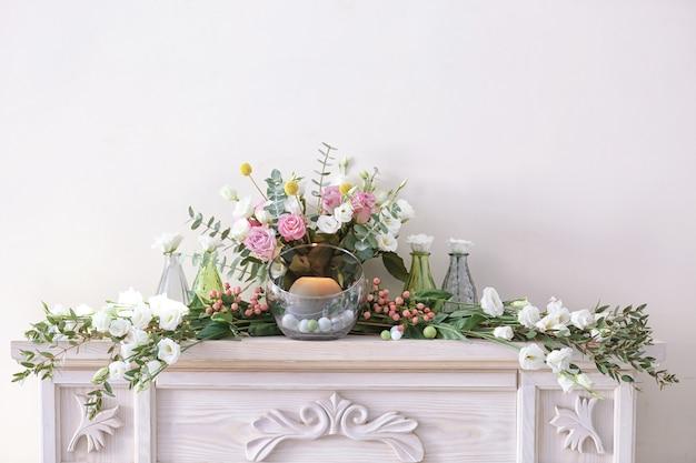 Bela composição com flores frescas e velas na lareira