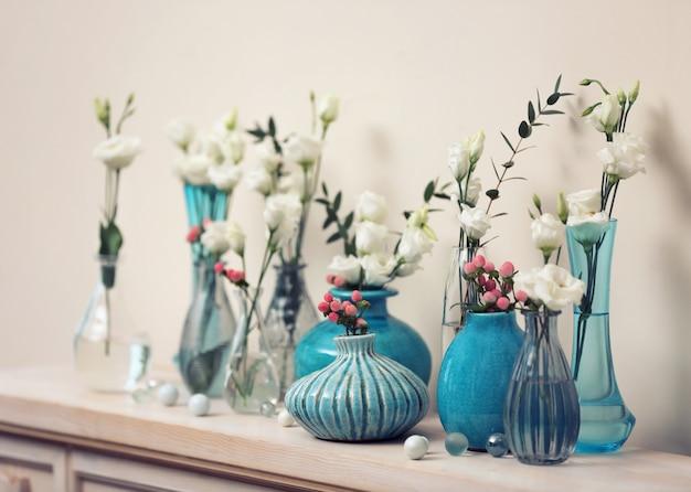 Bela composição com flores frescas em vasos na lareira