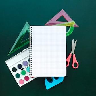 Bela composição com tesoura de caderno, régua e aquarelas sobre fundo verde de madeira